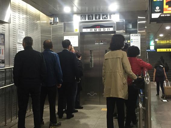 Des coréens font la queue devant un ascenseur dans le métro à Séoul.