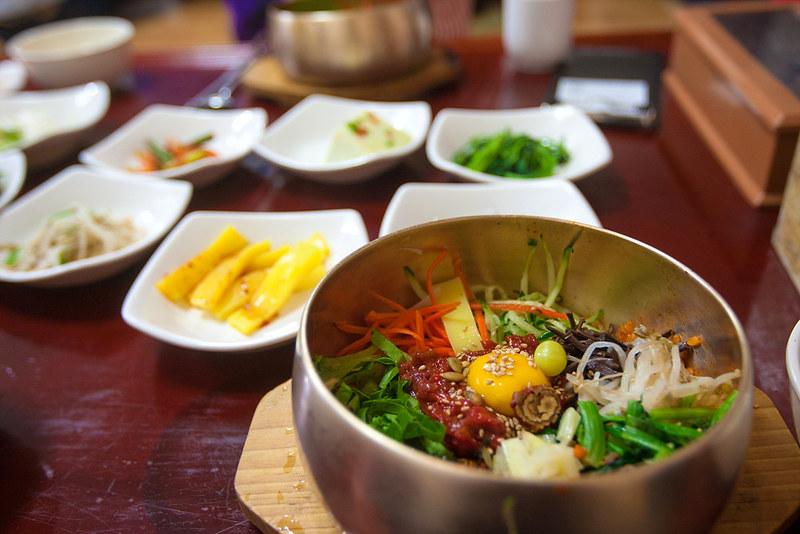 Bibimbap dans un bol en cuivre et ses banchans sur une table coréenne